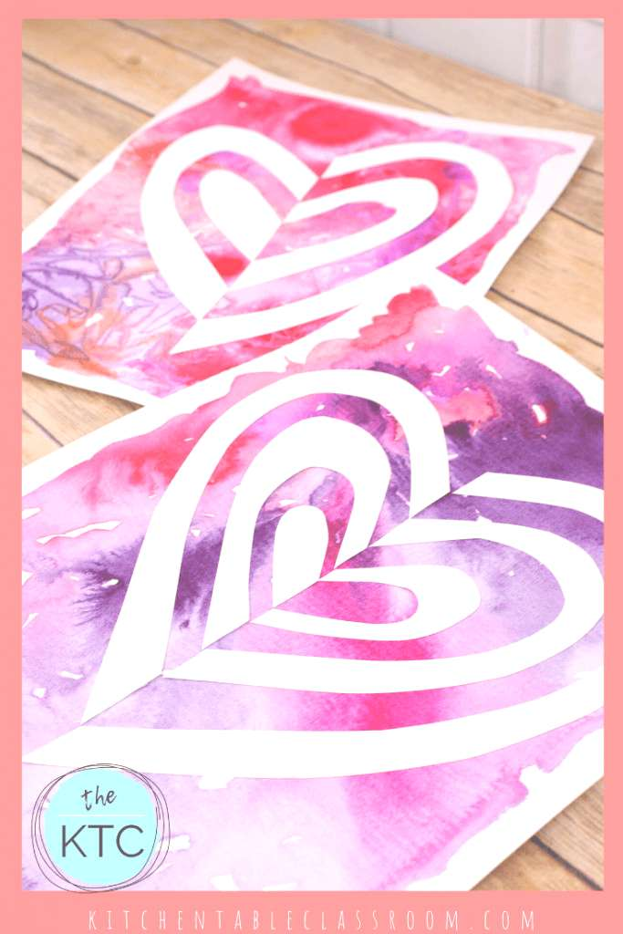 cut paper heart art with pink and purple watercolor background
